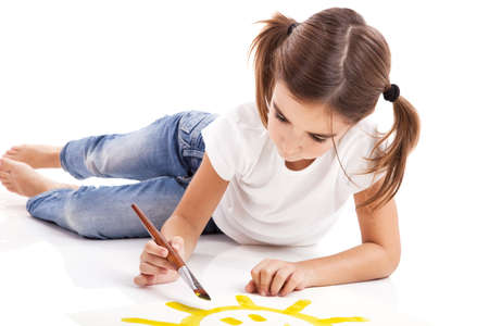 kids painting: Girl lying on floor and painting a happy sun