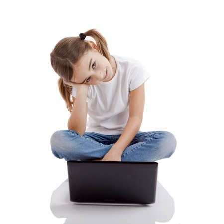 Little girl sitting on floor working with a laptop photo