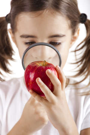 Little girl with a magnifying glass inspecting microbes on a red apple photo