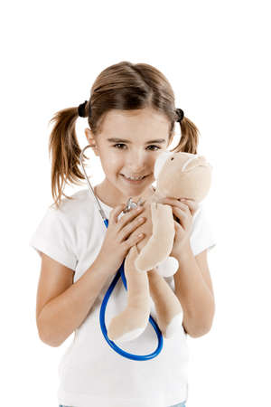 doctor toys: Beautiful little girl pretending to be a nurse and auscultate her teddy-bear  Stock Photo