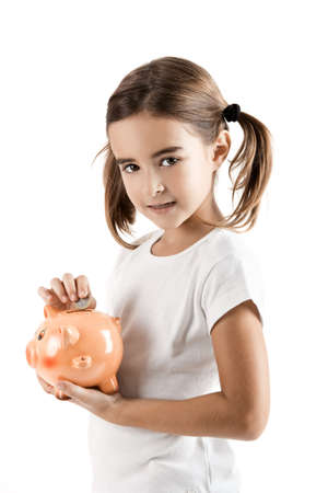 inserting: Little girl holding a piggy-bank and inserting a one euro coin