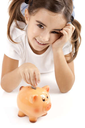 1 euro: Little girl lying on floor and inserting a one euro coin on the piggy-bank Stock Photo