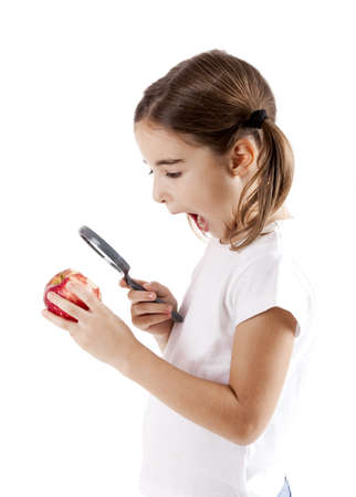 Little girl with a magnifying glass inspecting microbes on a red apple Stock Photo - 8990082