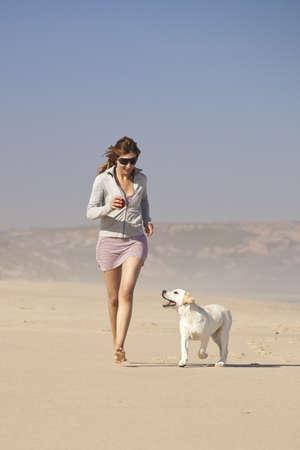 mujer con perro: Mujer joven que ejecutan y jugando con su cachorro lindo labrador retriever