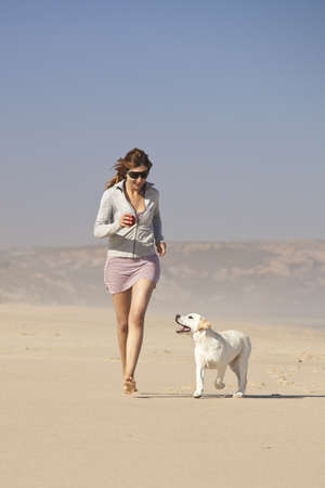 dogs play: Young woman running and playing with her cute labrador retriever puppy