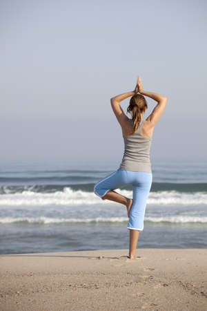 Beautiful young woman on the beach doing yoga exercises photo