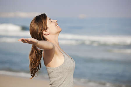 Beautiful young woman relaxing with arms open on the beach Stock Photo - 8990138