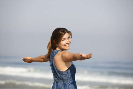 open  women: Beautiful young woman relaxing with arms open on the beach Stock Photo
