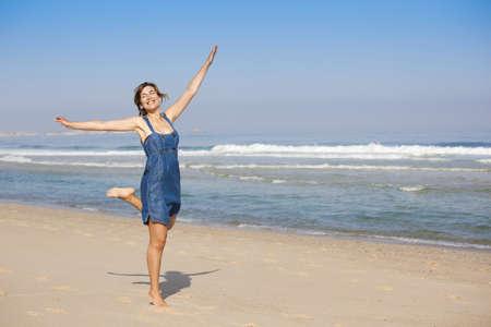 Beautiful happy young woman enjoying the beach photo