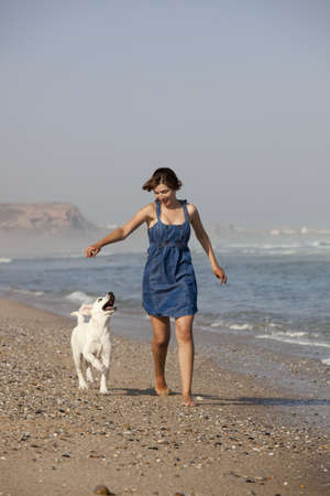 Young woman running and playing with her cute labrador retriever puppy  photo