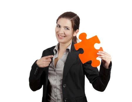 Business woman holding and pointing to a puzzle piece, isolated on white photo