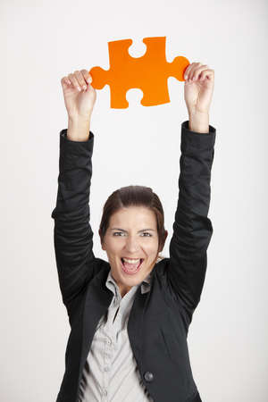 hands solution: Happy business woman holding a big piece of puzzle, isolated on white