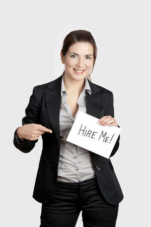 in need of space: Business woman holding a card board with the text message Hire me Stock Photo