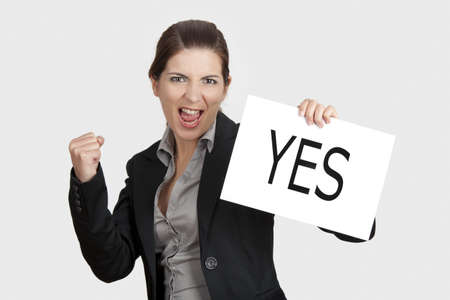 yes: Business young woman showing a paper card with the word YES Stock Photo