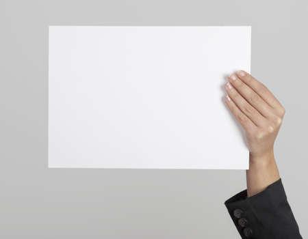 alzando la mano: La mano de una hoja de papel en blanco