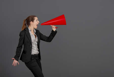 Business young woman speaking to a megaphone, over a grey background photo