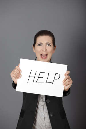 imploring: Stressed business woman imploring for help, holding a cardboard with the message Help. Focus is on the cardboard Stock Photo