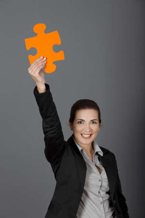 Business woman holding a big puzzle piece, over a gray background Stock Photo - 8990126