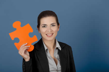Business woman holding a big puzzle piece, over a blue background Stock Photo - 8990136