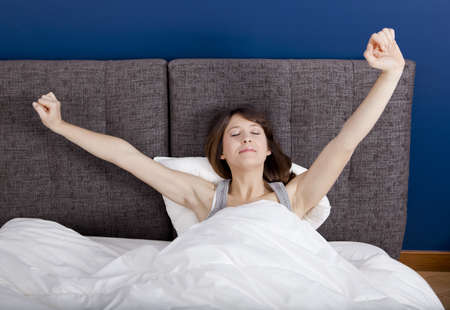 Beautiful young woman in pajama and lying on the bed with arms outstretched photo