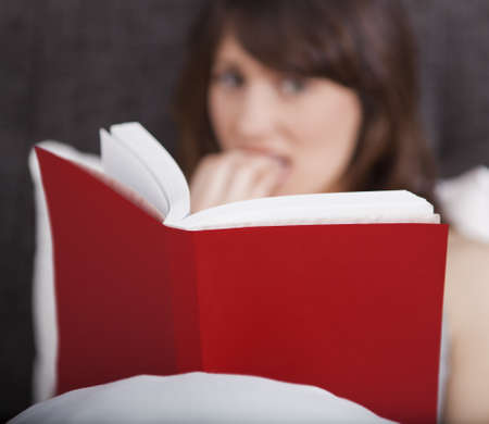 Young woman reading a terror storie with a terrified expression photo