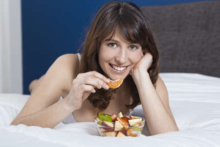 Beautiful and healthy young woman lying on bed and eating fruits photo