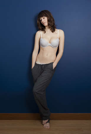 Beautiful young woman wearing a casual lingerie and pajama pants, against a blue wall Stock Photo - 9111974