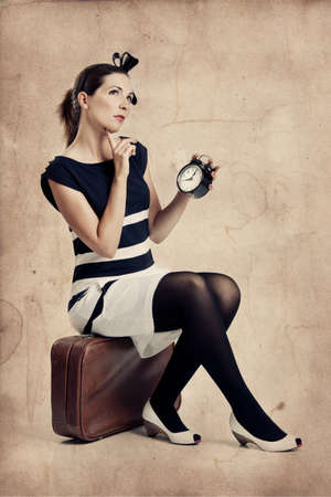 Beautiful young fashion woman sitting over a suitcase and holding a clock photo