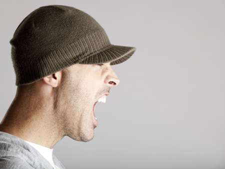 Profile portrait of a young man yelling, isolated on a gray background