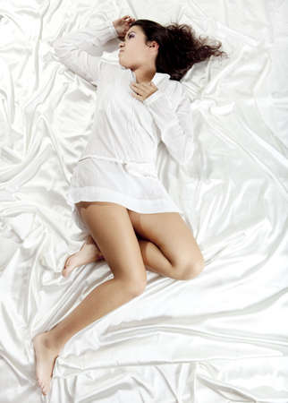 Beautiful and sexy young woman lying on a bed photo