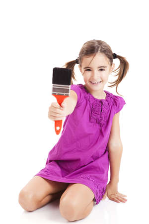little girl sitting: Happy girl sitting on floor holding a paint-brush  Stock Photo