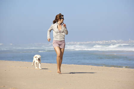 playing in the sea: Young woman running and playing with her cute labrador retriever puppy