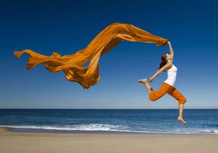 scarf beach: Joven y bella mujer saltando en la playa con un pa�uelo de color