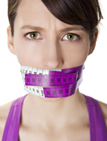Portrait of a young  woman with a measuring tape covering the mouth photo