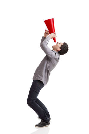 yell: Young man shouting into a megaphone over a white background