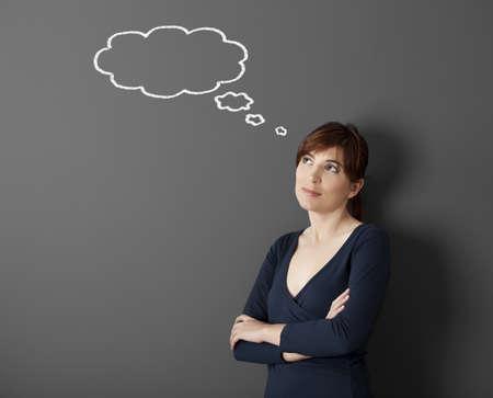 Joven pensando con un pensamiento un globo dibujado con tiza en la pared Foto de archivo