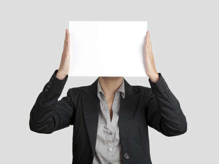 Woman showing a blank paper sheet in front of her head  photo