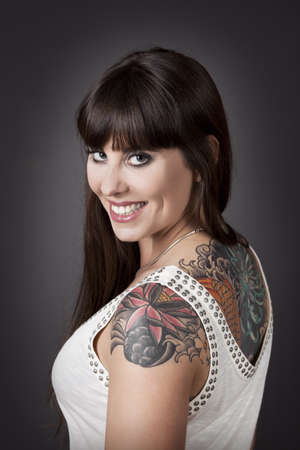 cute tattoo: Portrait of a beautiful young woman with a tattoo on the backs