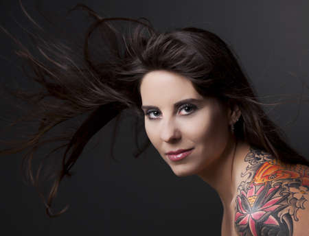 tattoos: Portrait of a lovely woman with a tatto on the shoulder against a grey background and spread hair