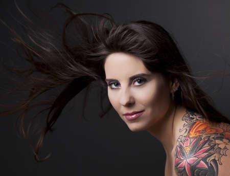 sexy tattoo: Retrato de una mujer encantadora con un tatto en el hombro contra un fondo gris y cabello de propagaci�n