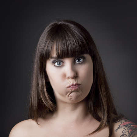 cheeks: Portrait of a beautiful and funny woman with cheeks full of air against a grey background Stock Photo