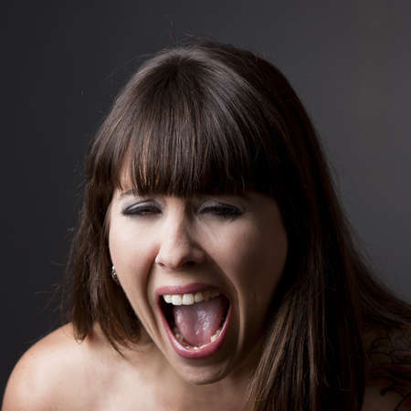 Close-up portrait of a desperate woman shouting with something, against a grey background photo