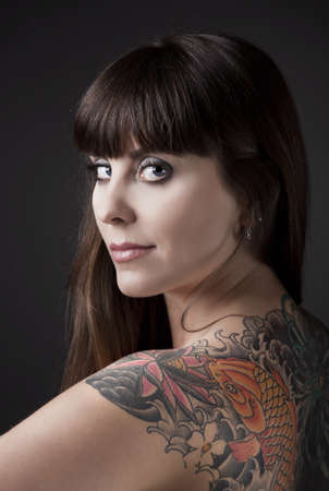 Portrait of a beautiful young woman with a tattoo on the backs Stock Photo - 9420872