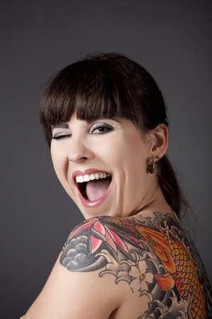 winking: Portrait of a beautiful young woman with a tattoo on the backs winking eyes
