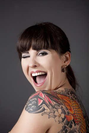 winking: Ritratto di una giovane donna bella con un tatuaggio sul dorso ammiccanti occhi