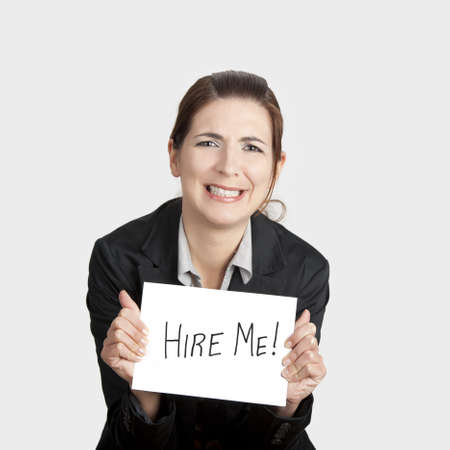 in need of space: Business woman holding a card board with the text message Hire me and beging for a job. Stock Photo