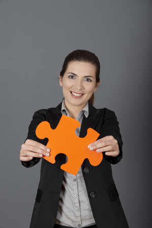 Business woman holding a big puzzle piece, over a gray background Stock Photo - 9420899