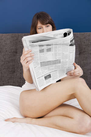 business woman legs: Beautiful young girl lying on the bed and reading the newspaper Stock Photo