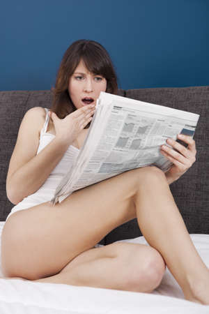 astonish: Happy young woman with a astonish expression reading the newspaper Stock Photo