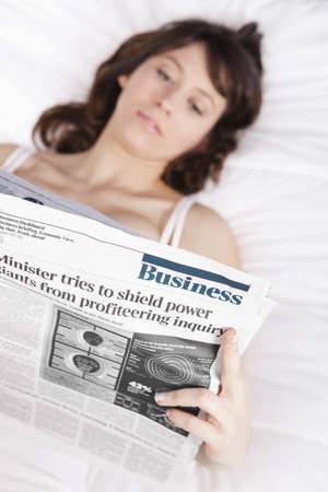 Happy young woman with a astonish expression reading a financial newspaper photo